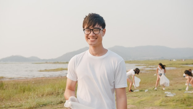 Portrait of young asia guy volunteers help to keep nature clean up, looking at front and smile with white garbage bags on the beach