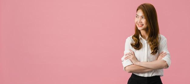 Ritratto di giovane donna asiatica con espressione positiva, braccia incrociate, sorriso ampiamente, vestita con abiti casual e guardando lo spazio su sfondo rosa.