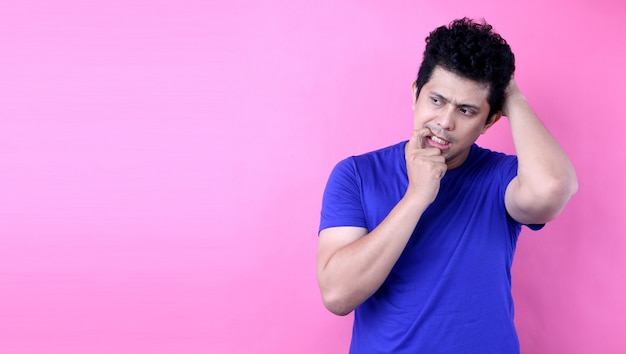 Portrait  young  asia man having doubts and with confuse face expression  on pink background in studio