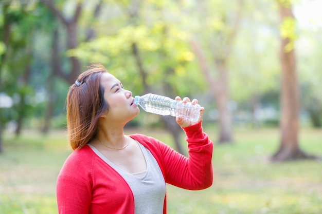 Portrait of young asian beautiful brown-haired woman wearing red t-shirt drinking water