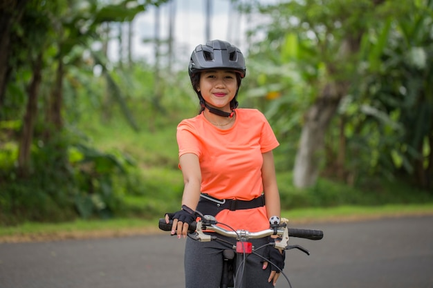 Portrait of young asian beautiful woman riding a bicycle