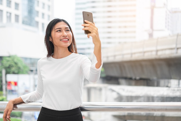Portrait of young asian beautiful woman taking selfie with smartphone in city of bangkok thailand