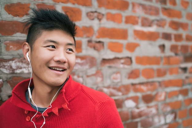 Portrait of young asian boy listening to music with earphones outdoors against brick wall
