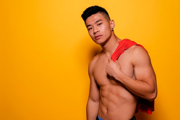 Portrait of young asian boy with fitness body. challenging attitude.