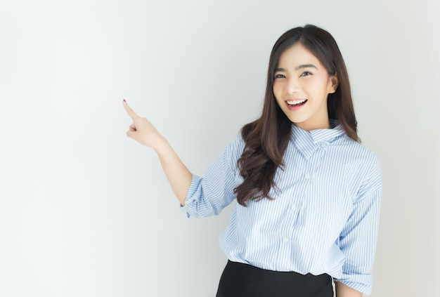 Portrait of young asian business woman pointing up over white background.