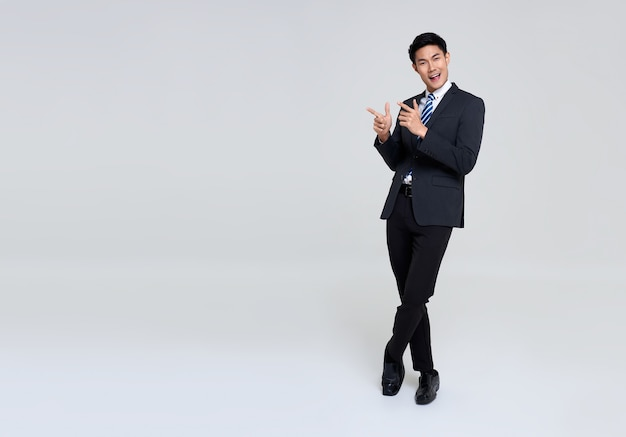 Portrait of young asian businessman hand pointing up to copy space on studio white.