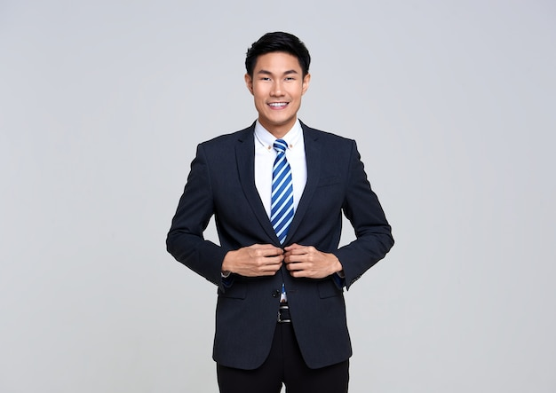 Portrait of young asian businessman smiling confidently while standing on studio white.