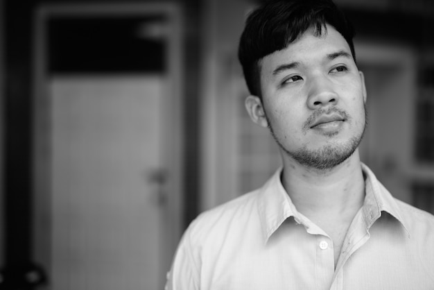 Portrait of young asian businessman thinking at home outdoors