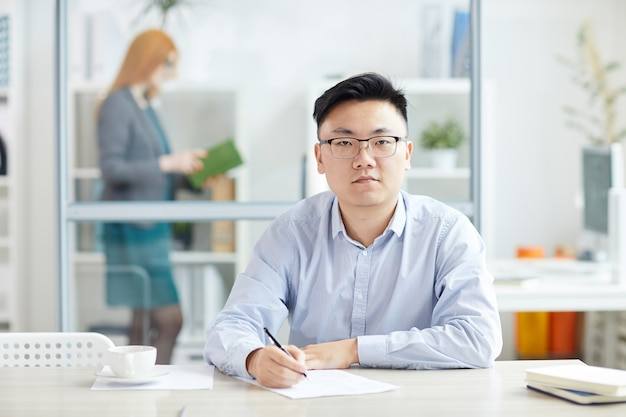 Portrait of young asian businessman wearing glasses while posing at workplace in office cubicle, copy space