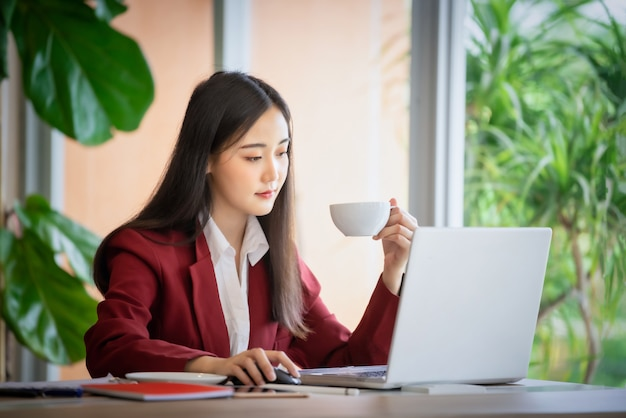 Portrait of young asian businesswoman sitting indoors in cafe drinking coffee using laptop computer. business success concept.