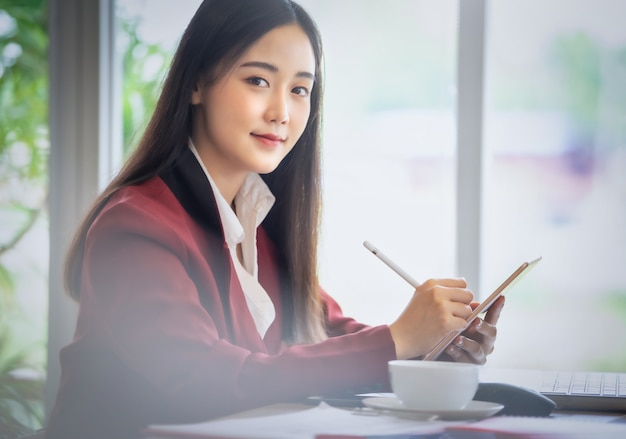 Portrait of young asian businesswoman sitting indoors in cafe using digital tablet with coffee. business success concept.