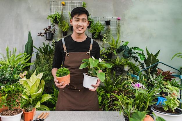 Ritratto di un giovane giardiniere asiatico in piedi e tiene in mano due bellissime piante d'appartamento, sorride e guarda la telecamera