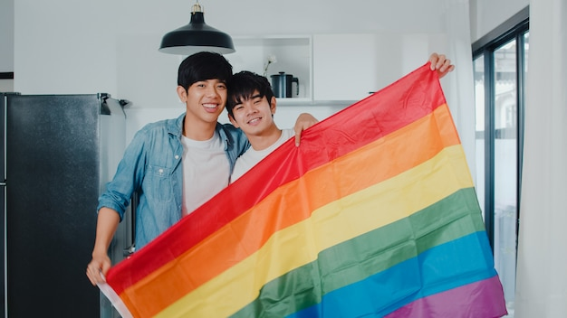 Portrait young asian gay couple feeling happy showing rainbow flag at home. asia lgbtq+ men relax toothy smile looking to camera while hug in modern kitchen at house in the morning .