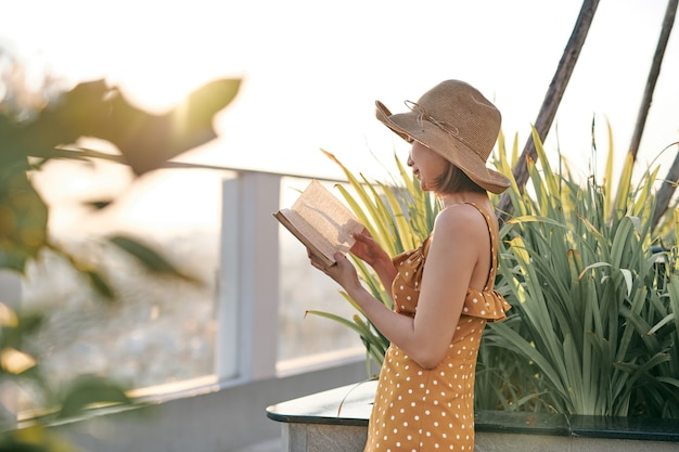 Portrait of young asian girl is reading book in roof top of building.