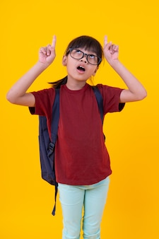Portrait of young asian girl student pointing up copy space