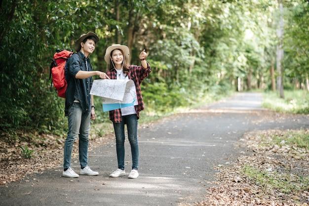Портрет молодой азиатский красивый мужчина с рюкзаком и треккинговой шляпой и симпатичная подруга, стоящая и проверяющая направление на бумажной карте, гуляя по лесной тропе, концепция путешествия рюкзака