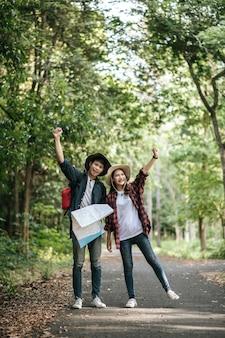 肖像画バックパックとトレッキング帽子とかわいいガールフレンドが立って、森の小道を歩きながら紙の地図で方向を確認している若いアジアのハンサムな男、バックパック旅行のコンセプト