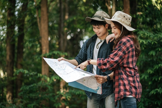 Portrait young asian handsome man with backpack and trekking hat and pretty girlfriend standing and checking direction on paper map while walking on forest trail, backpack travel concept