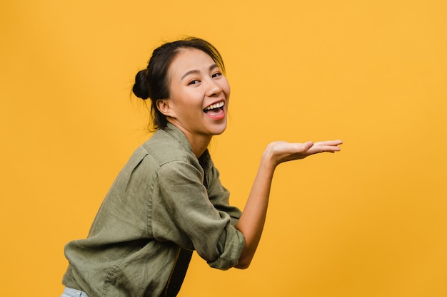 Ritratto di una giovane donna asiatica che sorride con un'espressione allegra, mostra qualcosa di straordinario in uno spazio vuoto in un panno casual isolato su un muro giallo. concetto di espressione facciale.