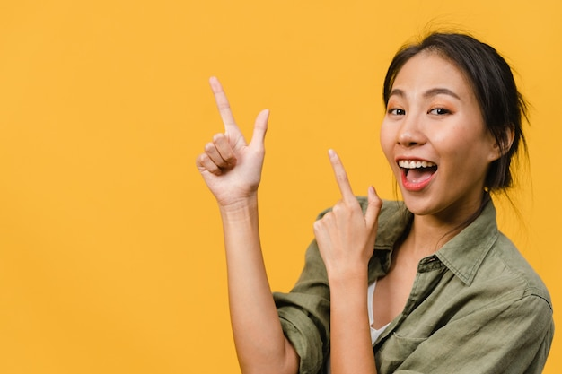 Portrait of young asian lady smiling with cheerful expression, shows something amazing at blank space in casual cloth  isolated over yellow wall. facial expression concept.