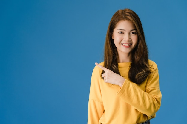 Portrait of young asian lady smiling with cheerful expression, shows something amazing at blank space in casual clothing and looking at camera isolated over blue background. facial expression concept.
