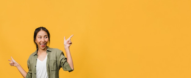 Portrait of young asian lady smiling with cheerful expression, shows something amazing at blank space in casual clothing and standing isolated over yellow wall. panoramic banner with copy space.