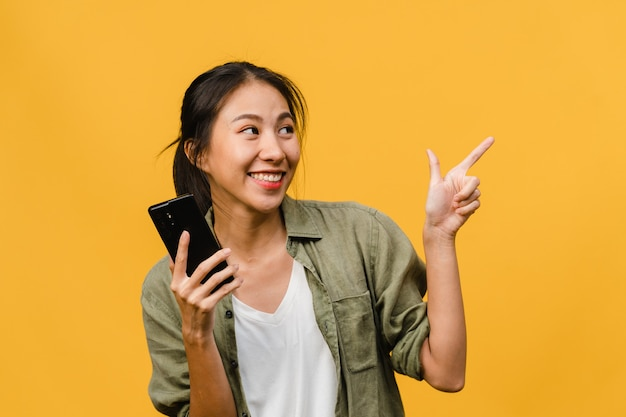 Portrait of young asian lady using mobile phone with cheerful expression, show something amazing at blank space in casual clothing and stand isolated over yellow wall. facial expression concept.