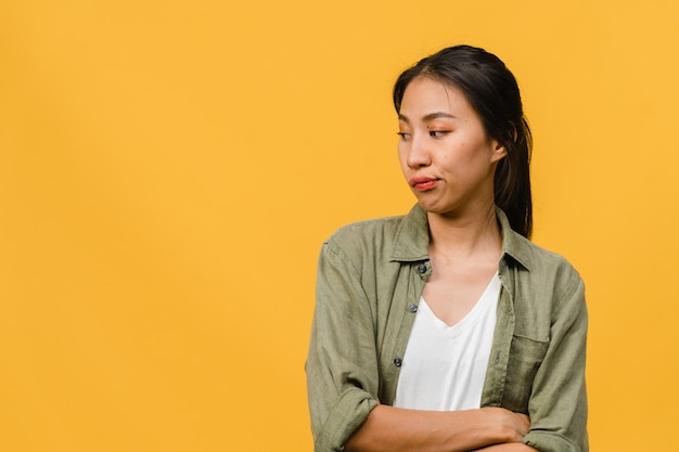 Portrait of young asian lady with negative expression, excited screaming, crying emotional angry in casual clothing isolated on yellow wall with blank copy space. facial expression concept.