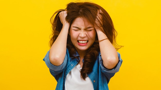 Portrait of young asian lady with negative expression, excited screaming, crying emotional angry in casual clothing and looking at the camera over yellow wall. facial expression concept.