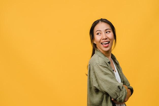 Ritratto di giovane donna asiatica con espressione positiva, braccio incrociato, sorriso ampio, vestito di stoffa casual sul muro giallo. la donna felice adorabile felice si rallegra del successo. concetto di espressione facciale.
