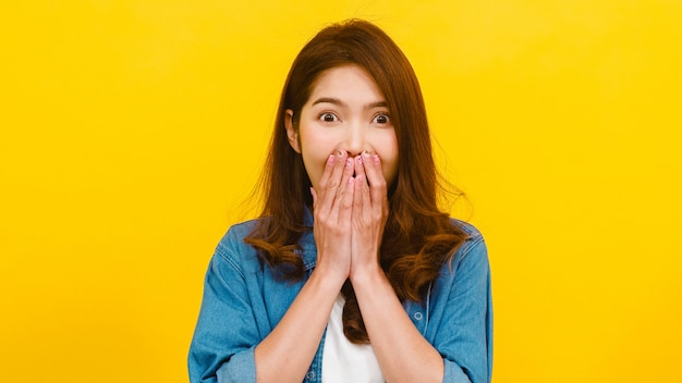 Portrait of young asian lady with positive expression, joyful surprise funky, dressed in casual clothing and looking at the camera over yellow wall. happy adorable glad woman rejoices success.