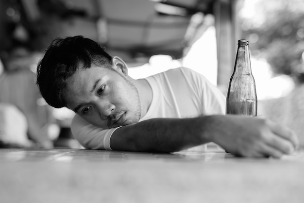 Portrait of young asian man getting drunk in the streets outdoors