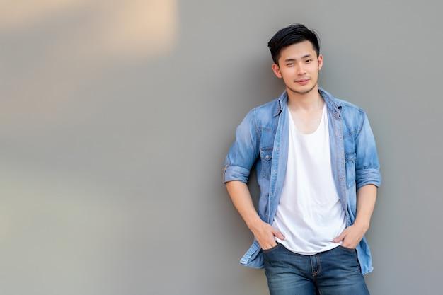 세로 젊은 아시아 남자. 미소 얼굴로 회색 벽에 기대어 주머니에 손 가진 잘 생긴 젊은 아시아 남자