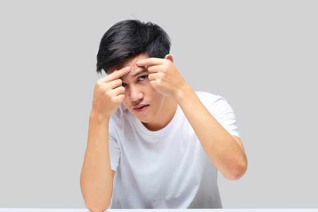Portrait of a young asian man using his hand squeezed a pimple on the forehead