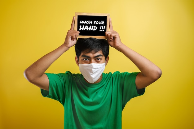 Portrait of young asian man wearing protective mask against the coronavirus, holding small blackboard written