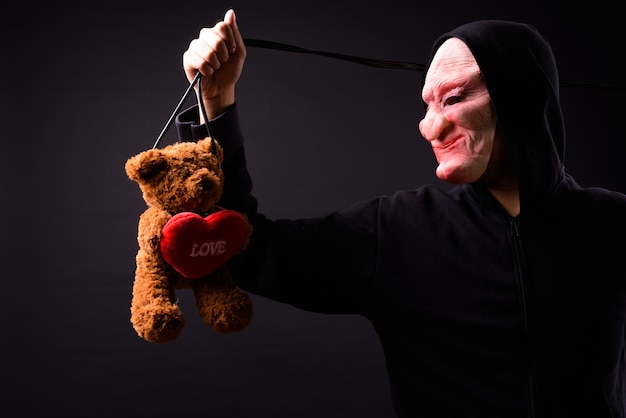 Portrait of young asian man with hoodie and horror mask on black