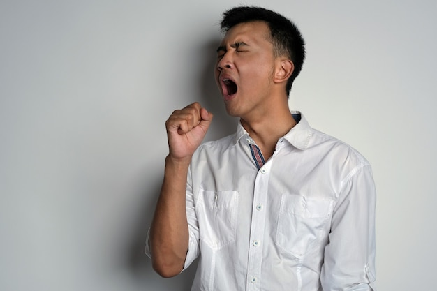 Portrait of young asian man yawning against white background young man feel sleepy