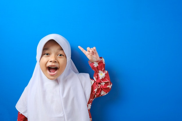 Portrait of young asian muslim girl looked happy, thinking and looking up, having good idea. half body portrait against blue background with copy space