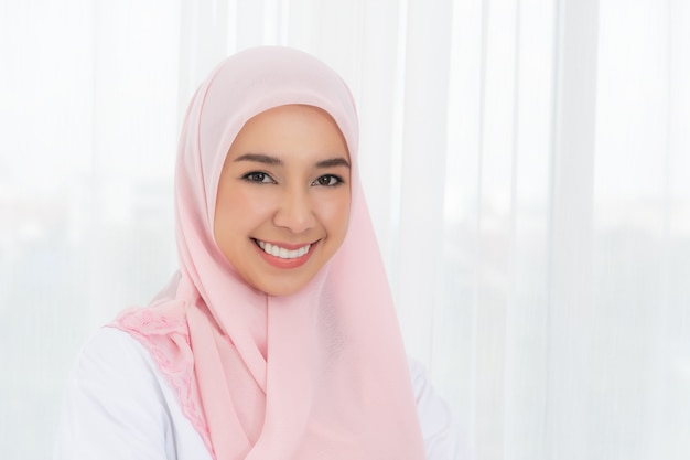 Portrait young asian muslim woman in pink headscarf smile with send kiss.