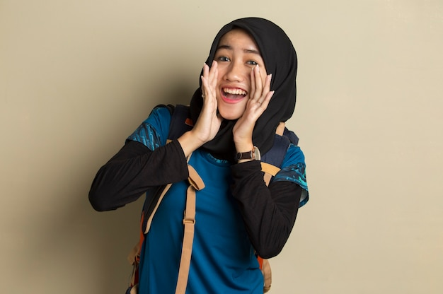 Portrait of young asian muslim woman traveler wearing hijab shouting and yelling