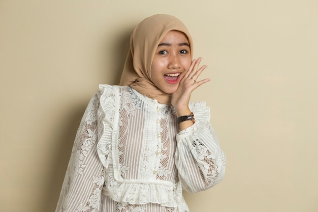 Portrait of young asian muslim woman wearing hijab feeling surprise to something