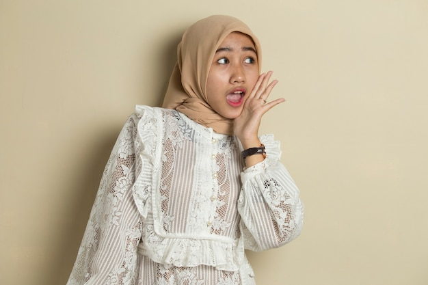 Portrait of young asian muslim woman wearing hijab shouting and yelling