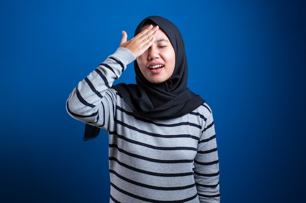 Portrait of young asian muslim woman wearing hijab shows regret gesture, hand on her forehead, forget something important, against blue background
