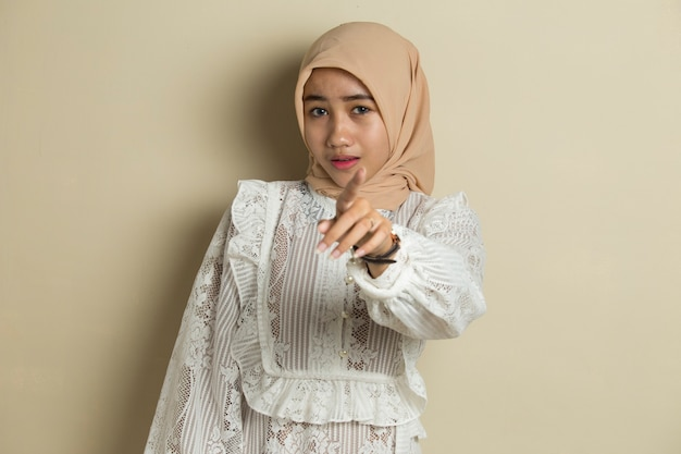 Portrait of young asian muslim woman wearing hijab smiling while pointing forward