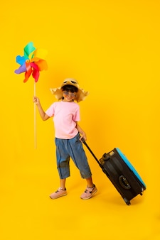Portrait of young asian pretty girl holding colorful turbine and drag blue travel bag on yellow
