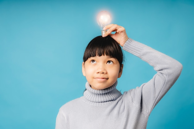 Portrait of young asian student and girl holding lighting bulb shinning on her head and thinking, idea and educational innovation of kid concept