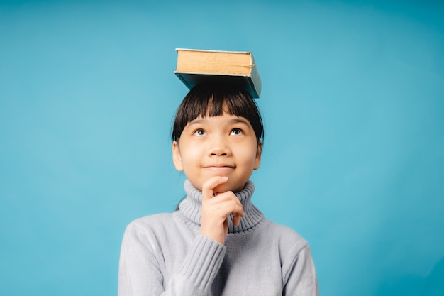 Portrait of young asian student and girl put big book on her head and thinking, idea and educational innovation of kid concept