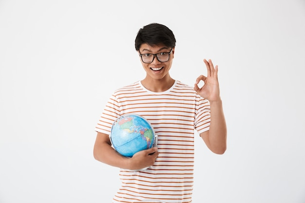 Portrait of young asian student man wearing striped t-shirt and eyeglasses holding globe and showing ok sign, isolated