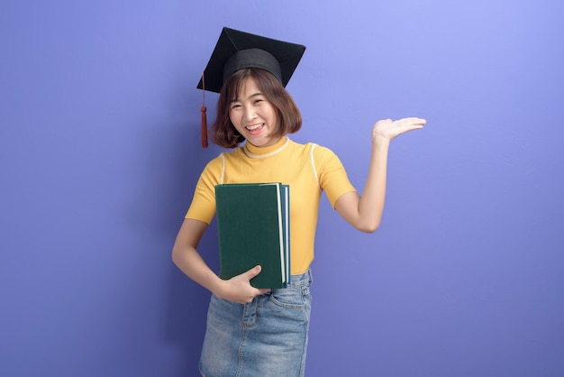 A portrait of young asian student wearing graduation cap over studio background.