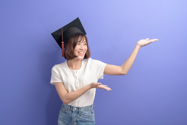 A portrait of young asian student wearing graduation cap over